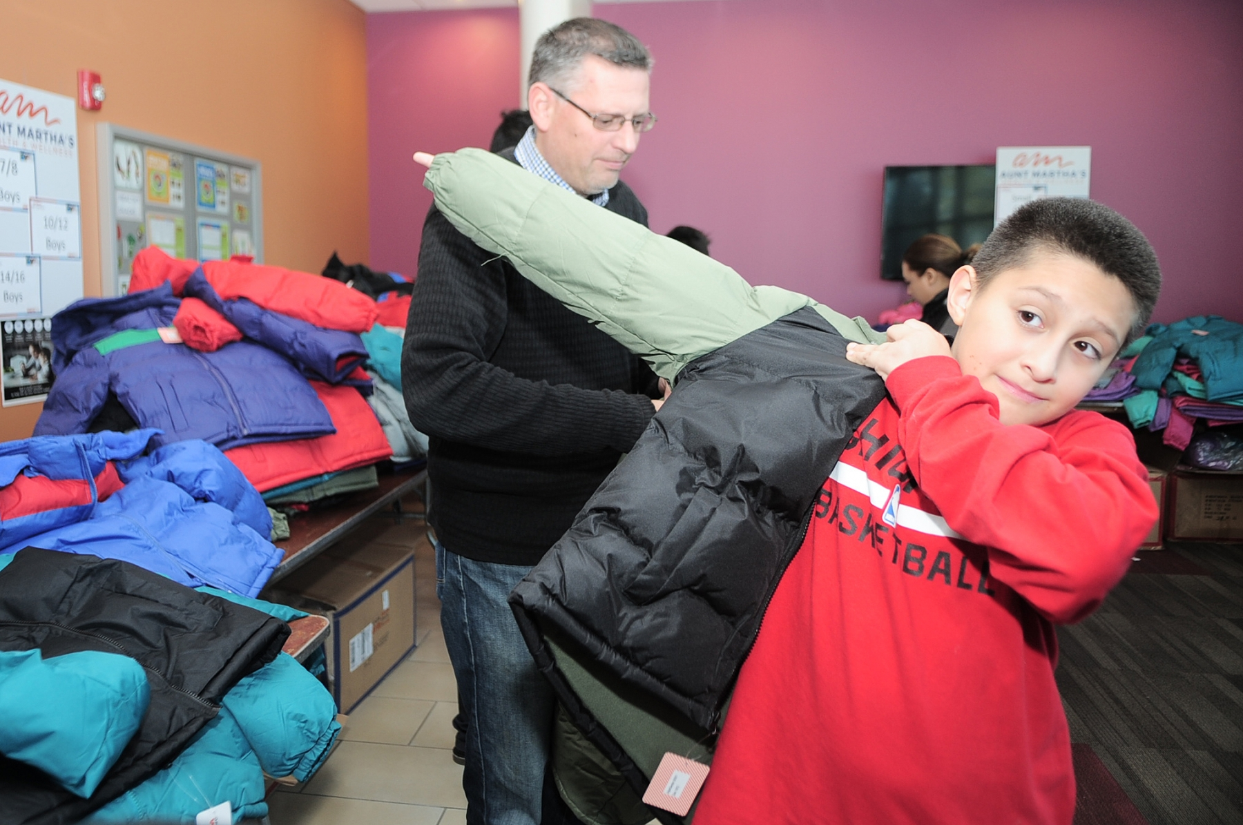 10-20-18 Aunt Martha's Clinic, coat drive and flu shots, Joliet IL Eduardo a boy from the Joliet community tries on a free winter coat he selected from the lot of 250 coats that Operation Warm gave away at Aunt Martha's Photo by John Booz