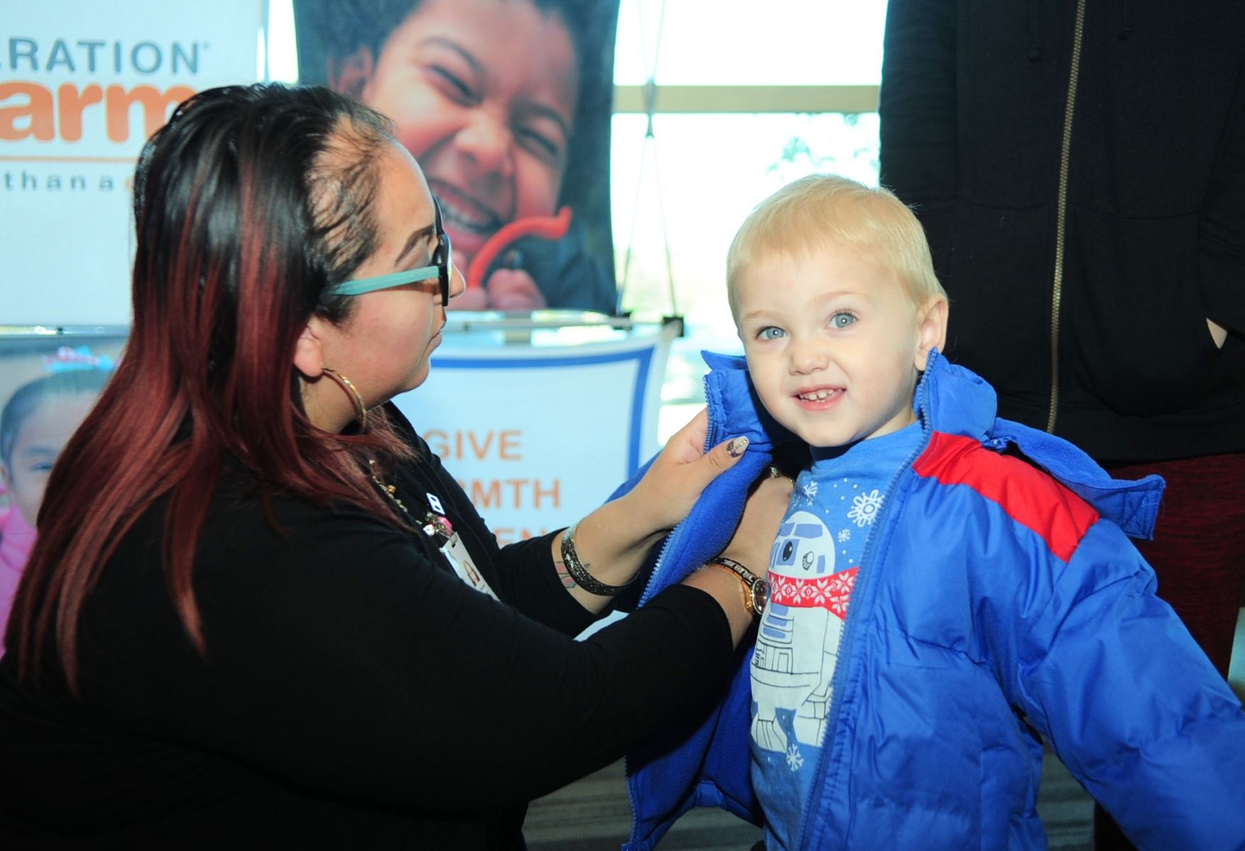 10-20-18 Aunt Martha's coat drive and flu shot campaign, Joliet IL Betsy Martinez from Aunt Martha's South Chicago clinic, helps young Dylan Wheeler (3) to find a fitting free winter coat donated by Operation Warm. Photo by John Booz